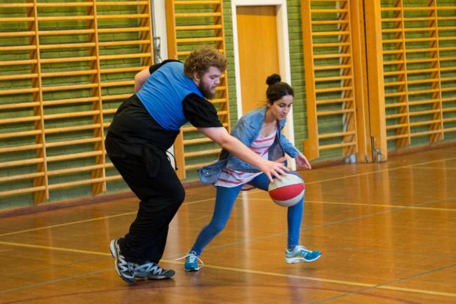 Skjeggete mann spiller basket mot kvinne